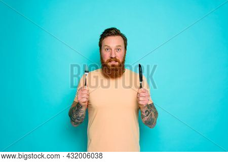 Happy Man With Tattoos Is Ready To Eat With Cutlery In Hand