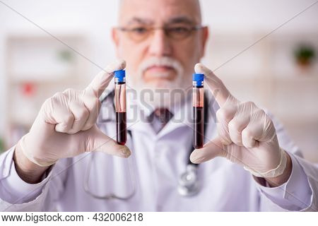Old male doctor hematologist working in the clinic