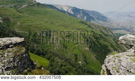 Top View Of Rocky Cliffs Above Green Mountain Valley. Action. Beautiful Landscape With High Green Mo