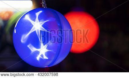 Transparent Balls With A Handle Inside Contain An Led Bulb. Illuminated Led Christmas Ball On Dark B