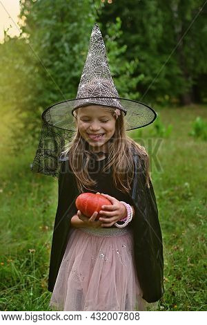Happy Halloween Day. Little Girl Dressed In Witch Costume Holds Pumpkin And Fun Smiling In Autumn Pa