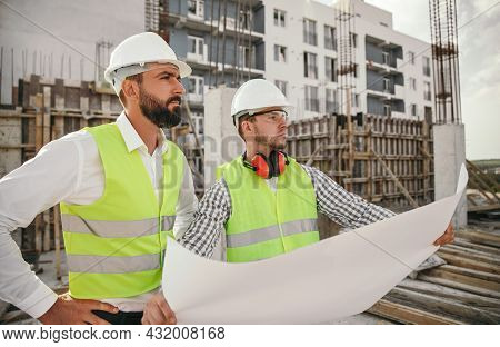 Serious Multiracial Male Construction Manager And Engineer In Hardhats And Waistcoats Checking Bluep