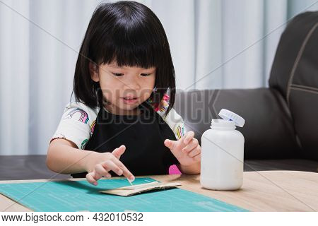 Sweet Child Girl Applying Pieces From Cardboard Boxes Using Glue While Doing Arts And Crafts At Less