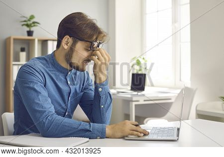 Stressed Tired Office Worker Has Eye Strain From Constant Work On Laptop Computer