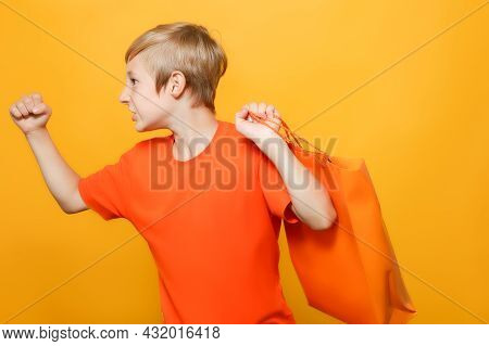 The Boy Threw An Orange And A Paper Shopping Bag Over His Back And Shows His Fist To The Side