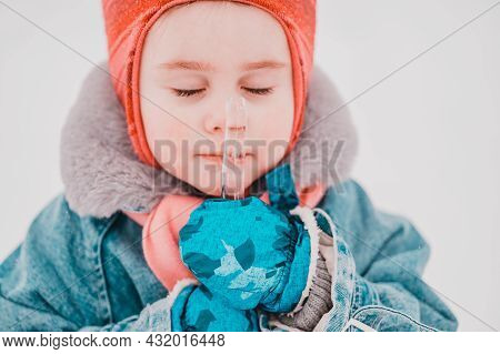The Little Girl Holds An Icicle In Her Hands And Presses It To Her Face,