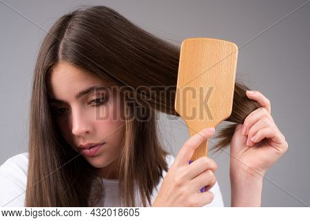 Sad Girl With Damaged Hair. Hair Loss Problem Treatment. Portrait Of Woman With A Comb And Problem H