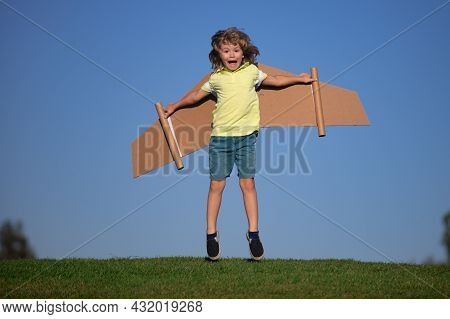Funny Child Boy Playing With Plane Wings Outdoors. Cute Boy Playing Pilot And Dreaming Of Becoming A