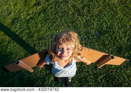 Child Boy Dreams And Travels On Green Grass In Park. Boy With Airplane Toy Outdoors. Happy Child Pla