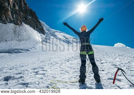 Woman Raised Her Arms And Greeting Bright Sun And Blue Sky While Ascending Mont Blanc (monte Bianco)