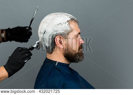 Bearded Man Color Hair. Process Of A Man Hair Coloring At Hairdresser Salon.