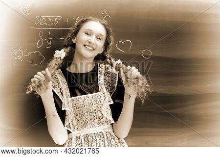 Retro Shot Of Joyful School Girl In Uniform. Happy Girl Standing In Front Of Blackboard Holding Her