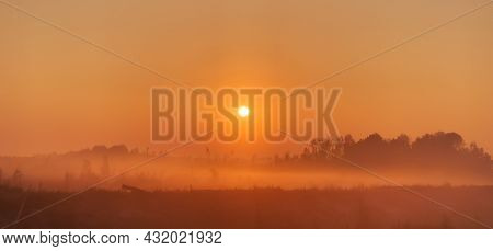 A Bright Sun Rises In The Fog Over The Tundra And Forest. Landscape, Panorama, Blurred Soft Focus.