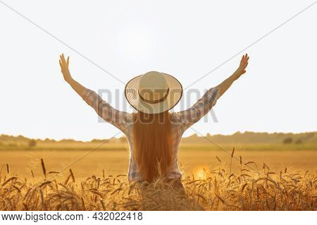 Rear View Silhouette Of Woman With Hat On Farmers Head With Hands Raised Up At Sunset.