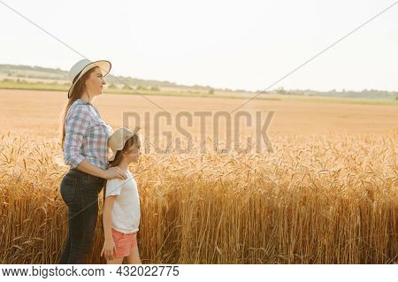 Side View Of A Family Of Farmers Woman Mother And Kid Daughter Both With Hats On Their Heads Near A