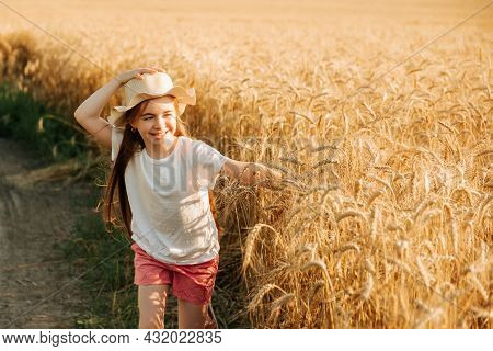 Adorable Little Girl Runs Happily On The Road Near The Yellow Wheat Field. Child With A Way Of Life