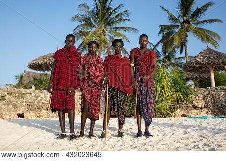 Zanzibar, Tanzania, January 27, 2021: Four Masses In Traditional Red Clothes Are Standing On The Bea