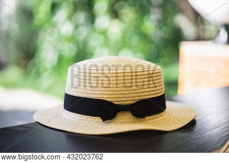 Hat On The Table. Straw Lady's Hat With A Black Ribbon. Concept Of Rest And Vacation. Table In A Par