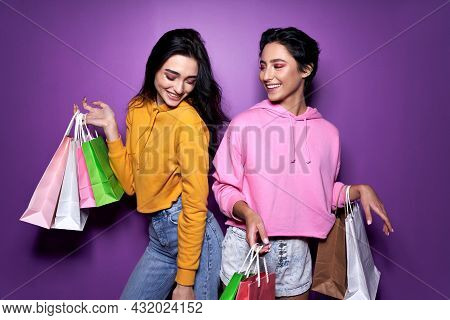 Two Happy Pretty Girls Friends Shoppers Holding Shopping Bags, Female Teenage Shopaholics Standing O