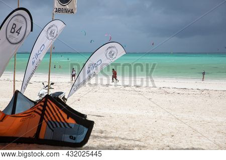 Zanzibar, Tanzania, January 22, 2021: Beach For Surfers, Turquoise Sea, People Walking Along The Bea