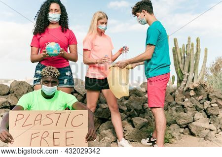 Group Of Activists With Banners Protesting Over Pollution On The Coast Line. Teenagers Doing A Silen