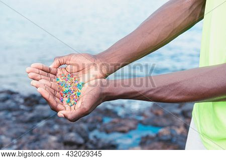 Hands Full Of Microplastics On The Beach. Different Plastic Colored ... Plastic Pollution Concept.