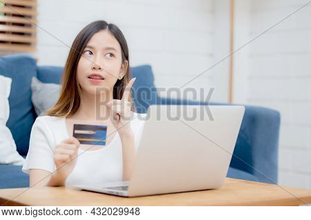 Young Asian Woman Sitting Thinking Idea Using Credit Card With Laptop Computer On Couch, Girl Shoppi
