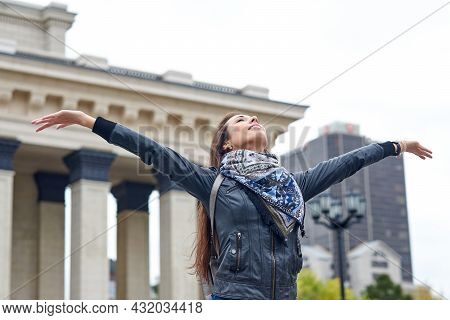 Happy Woman Standing With Her Arms Outstretched On Background Of Architecture Of Urban City