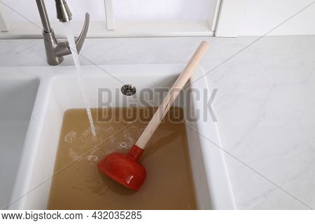 Clogged Kitchen Sink With Plunger And Dirty Water