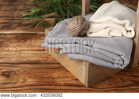 Hemp Cloths And Woolen Yarn In Crate On Wooden Table, Space For Text