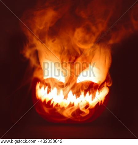 Fiery red hot Halloween jack o lantern pumpkin carved with scary evil face glowing brightly with thick smoke.