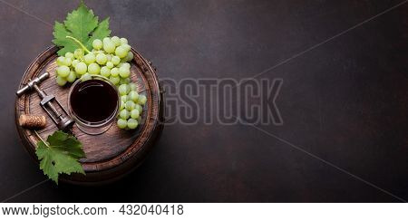 White grape, vintage corkscrew and red wine glass on old wooden wine barrel. Top view flat lay with copy space