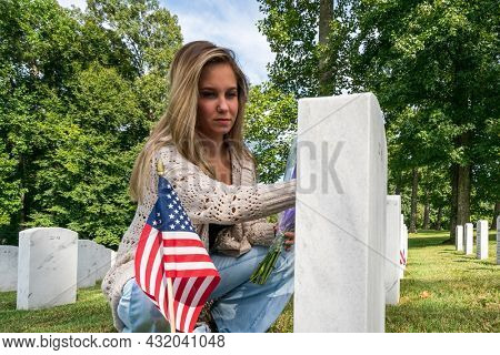 A young bride shows her grief at the burial site of a family member at a military cemetery