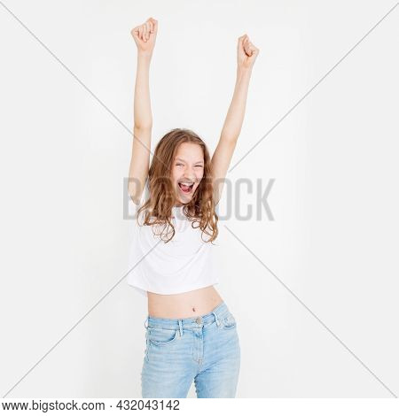 Young woman wearing casual white t shirt with a happy and cool smile on face. lucky person Cheerful happy girl looking at camera laughing over white background. Happy win teen