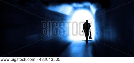 Long tunnel walkway with person at the end in motion ending depression towards the light