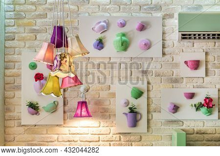 Bunch Of Pendant Lamps Against Brick Wall With Decorative Panels
