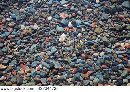 Underwater Pebble Stones Background. Colorful Sea Pebble Stones Texture With Clear Sea Water.