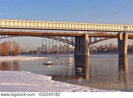 Three Bridges Over The Ob River In The Morning, Snow And Ice On The Bank, High Houses On The Horizon