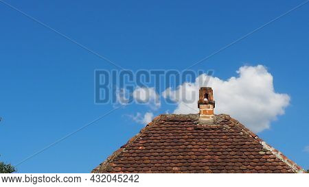 Red Roof With A Chimney Under The Blue Sky And White Clouds. Traditional Rustic Tiled Roof. Serbia,