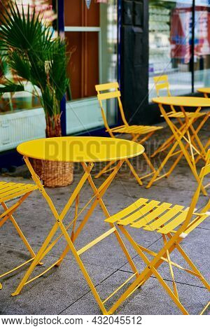 Yellow Decorative Table And Chairs At Cafe In City Street. Street Cafe In European City.