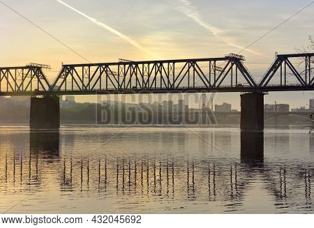 Early Morning On The Great Siberian River, Golden Dawn With Clouds, A City On The Bank In The Distan