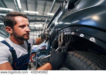 Mechanic Fixating Screw Clamp On Car Body