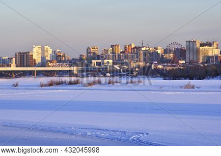 A Big City On The Banks Of The Frozen Great Siberian River Covered With Snow. Tall Houses Bridges In