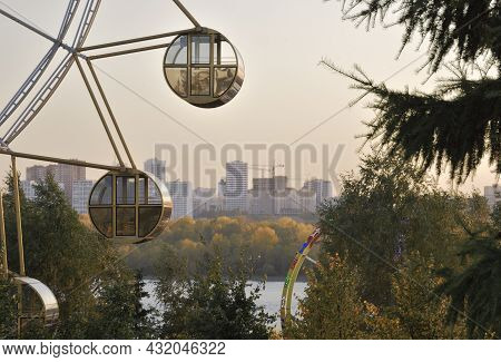 Ferris Wheel In The Park Of Novosibirsk. Round Cabs Ferris Wheel On The Embankment Of The Ob River A