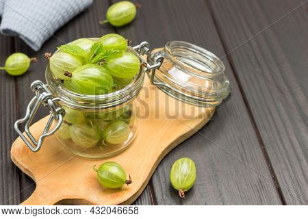 Green Gooseberry Berries In Glass Jar And On Wooden Board. Berry On Table. Top View. Wooden Backgrou