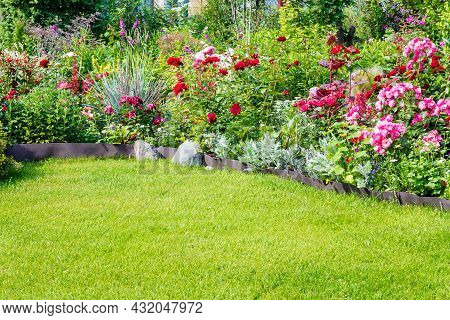 A Beautiful Blooming Well-groomed Fragment Of A Summer Garden With A Variety Of Flowers And A Green