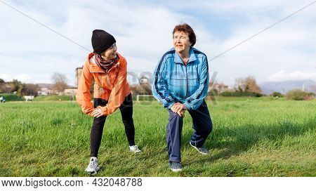 Smiling Grandmother And Granddaughter Doing Sports Together In The Park. Old And Young Women In Spor