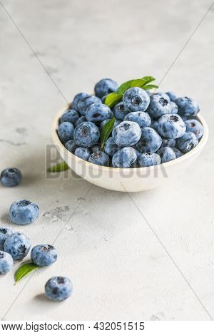 Freshly Picked Blueberries In A  Bowl. Juicy And Fresh Berries With Green Leaves On A Rustic Table.