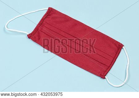 Dark Red Protective Textile Face Mask Lies On A Blue Surface