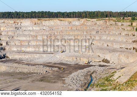 Operating Quarry For The Extraction Of Gray Granite Among The Forest, Fragment Of Quarry Slope With